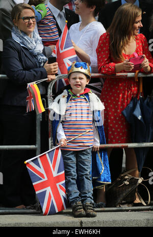 Berlin, Germany. 26th June, 2015. A boy dressed in a king's costume looks on as Britain's Queen Elizabeth II walks across Pariser Platz square in Berlin, Germany, 26 June 2015. The British monarch and her husband are on their fifth state visit to Germany from 23 to 26 June. PHOTO: KAY NIETFELD/dpa Credit:  dpa picture alliance/Alamy Live News Stock Photo