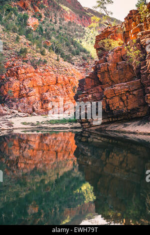 Reflection in water of red rocks at Ormiston Gorge in the West MacDonnell Ranges - Stock Photo