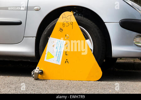 A wheel clamp fitted by the DVLA to a car whose keeper has not paid vehicle tax / has valid TAX disc. UK. - Stock Photo