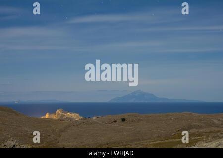Myrina city lit castle and holy Mount Athos on horizon in full moon. View from Mt. Kakavos / Panagia Kakaviotissa - Stock Photo