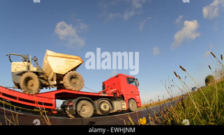 worms eye view of articulated low loader lorry traveling on country road near leeds yorkshire uk - Stock Photo