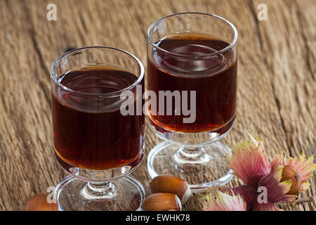 Homemade Hazelnut liqueur in two glasses and hazelnuts on ...