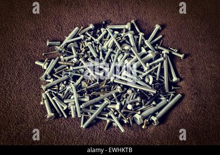Group of screws. Bolts, nuts, screws in a pile on dark background. - Stock Photo