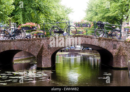 Bicycles parked on a bridge over a canal in Den Haag, The Hague, Netherlands - Stock Photo