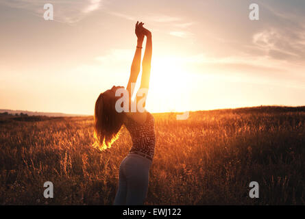 Free happy young woman raising arms at sunset in the field in summer. Background - Stock Photo