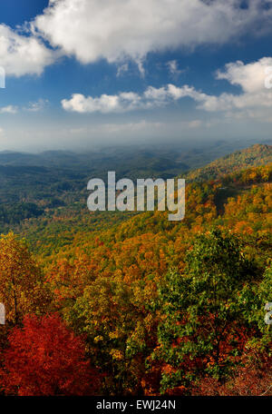 The sun rises over the mountains of Great Smoky Mountains National Park at the peak of autumn's colors. - Stock Photo