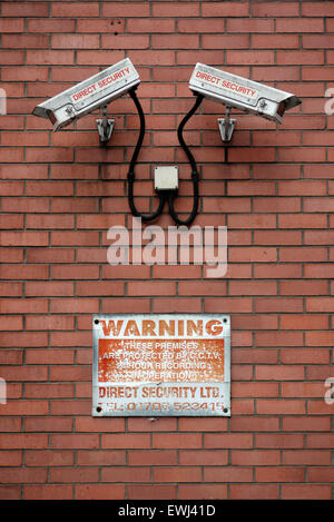 A pair CCTV surveillance security cameras on the outside wall of a building in England UK - Stock Photo
