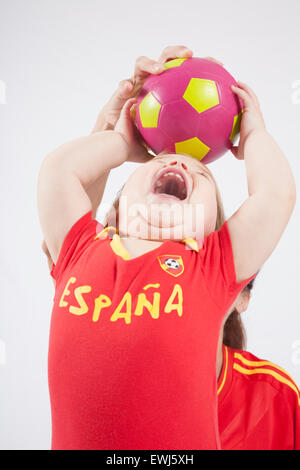 blonde baby sixteen month old and mother with red shirt of Spanish soccer team taking ball - Stock Photo