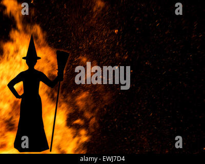 Witch silhouetted against bonfire. - Stock Photo