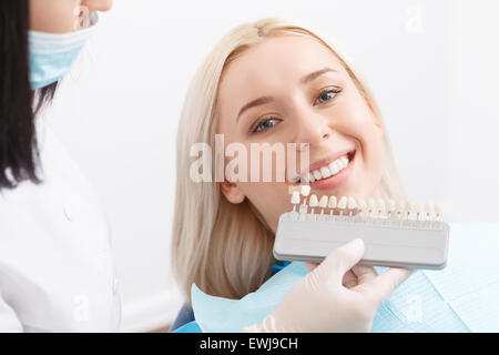Dentist matching filling for teeth of his client - Stock Photo