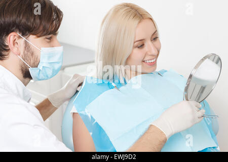 Patient checking completed work of dentist - Stock Photo