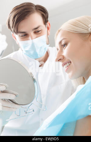 Smiling woman looking in mirror by dentist - Stock Photo