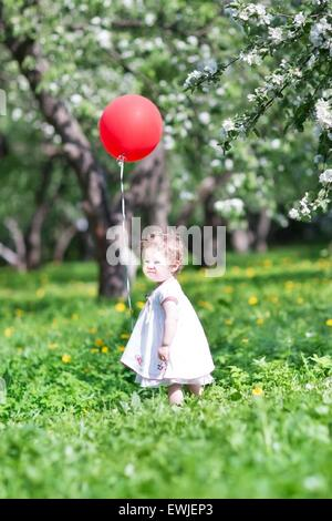 Funny baby girl playing with a big red balloon - Stock Photo