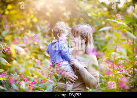 Beautiful woman playing with a laughing baby girl on sunset in a garden with pink and red flowers - Stock Photo