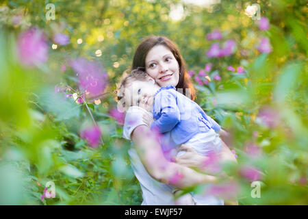 Young pregnant mother holding her tired baby daughter in a park with beautiful pink and purple flowers at sunset - Stock Photo