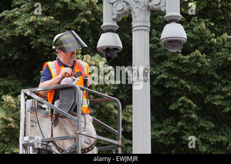 Technician installing outdoor security camera system - USA - Stock Photo