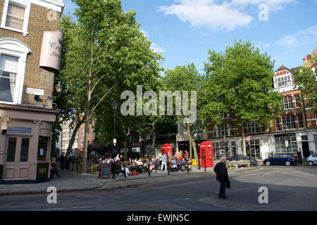 Crowds relaxing in the sun on Clerkenwell Green, London - Stock Photo