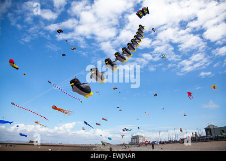 Morecambe, Lancashire, UK 27th June, 2015. Catch The Wind Kite Festival an annual festival on Morecambe seafront, when for the whole day the skies are full of the most spectacular shapes, colours and creations.  Featured were single line kites of all kinds and sizes, including a massive 30 metre long inflatable flying penquins. Stock Photo