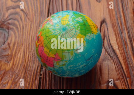 on a wooden board is the ball, which shows the world - Stock Photo