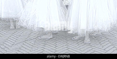 Little girls dressed up as bridesmaids, participating in a wedding, wearing gauze skirts, gray flip-flops and red - Stock Photo