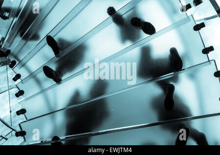 Feet on a glass staircase looking upwards from below the stairs.  Staircase is in a high-profile New York store - Stock Photo