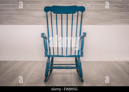 Blue rocking chair on a wooden floor - Stock Photo