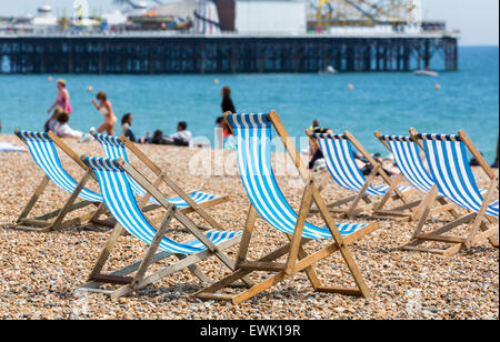 Traditional old-fashioned blue and white striped deckchairs on the beach in front of the Palace Pier, Brighton, - Stock Photo