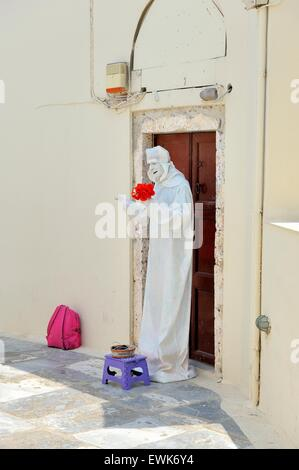 A street artist dressed in white holding some red flowers in the village of Oia Santorini,Greece. - Stock Photo