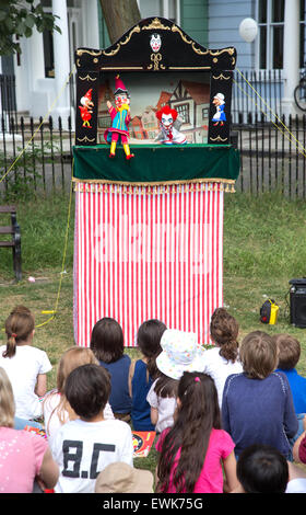 Children watch a traditional Punch and Judy show - Stock Photo