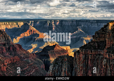 Evening sun breaks as spring storm builds over the North Rim of Arizona's Grand Canyon National Park from Walhalla - Stock Photo