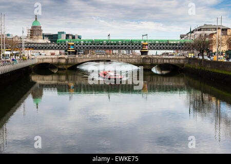 Dublin Tour Boat passes underneath the Rosi Hacket Bridge on the Liffey. - Stock Photo