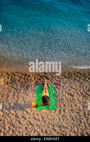 Woman lying on the beach - Stock Photo