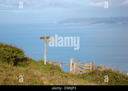 Signpost and Kissing Gate on the South West Coast Path, overlooking Lyme Bay. Dorset. England. UK. - Stock Photo