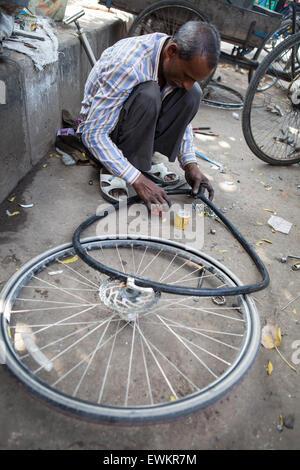 Bicycle repair man mending a puncture in Delhi - Stock Photo