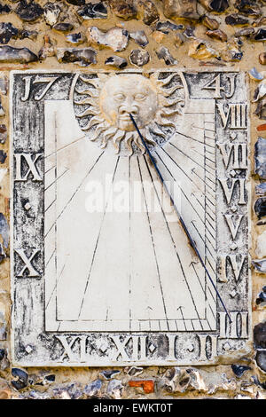 Ickham, England. 14th century village Church of Saint John the Evangelist. Sundial on side of church wall - Stock Photo