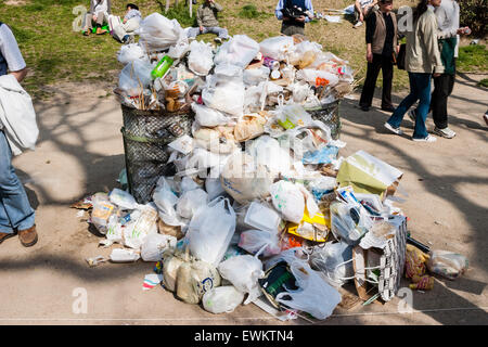 Japan, Shukugawa. Litter bin in park, filled and surrounded by plastic bags full of rubbish and garbage - Stock Photo