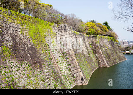 Japan, Osaka castle. View along moat with high stone walls. Clear blue sky - Stock Photo