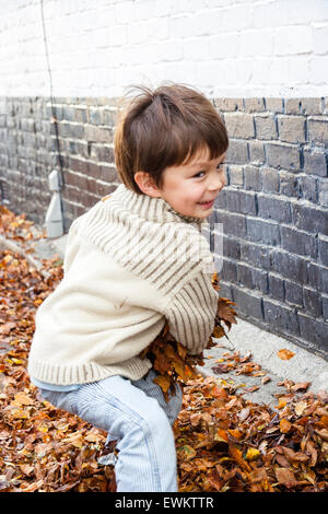 Close up of caucasian child, boy, 5-6 years, outdoors in street by a painted brick wall, turning and about to throw - Stock Photo