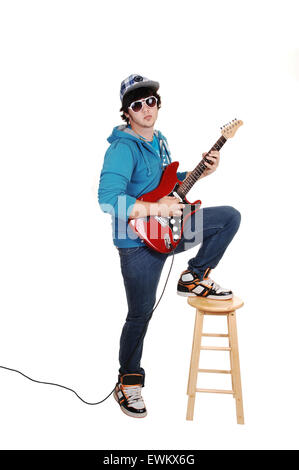 A teenage boy standing and playing the guitar in jeans and a cup with a blue sweater and sunglasses, on a white - Stock Photo