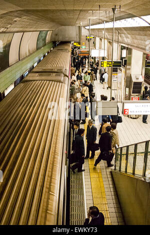 Interior of Japanese subway station in Osaka. Overhead view of people on platform with train, while passengers are - Stock Photo