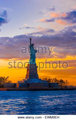 Statue of Liberty at sunset, New York Harbor, New York, New York USA. - Stock Photo