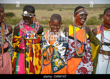 Masai women wearing colorful traditional dress, singing, laughing and smiling in a village near the Masai Mara, - Stock Photo