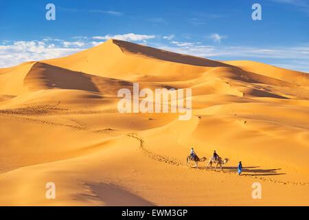 Morocco - tourists ride on camels, Erg Chebbi desert near Merzouga, Sahara - Stock Photo