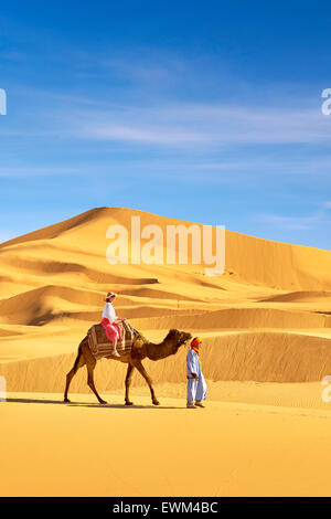 Tourist on camel ride, Erg Chebbi desert near Merzouga, Sahara, Morocco - Stock Photo