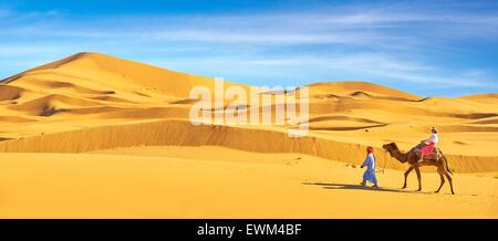Tourist on camel ride, Erg Chebbi desert near Merzouga, Sahara, Morocco - Stock Photo