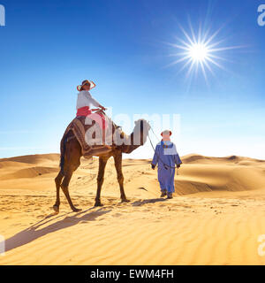 Tourist on camel ride, Erg Chebbi desert near Merzouga, Sahara dunes, Morocco - Stock Photo