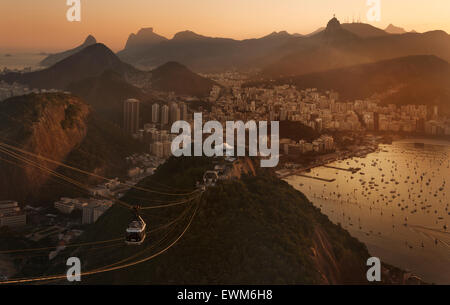 Christ the Redeemer atop Mount Corcovado and the cable car from Sugarloaf (Pao de Acucar) in Rio de Janeiro, Brazil - Stock Photo