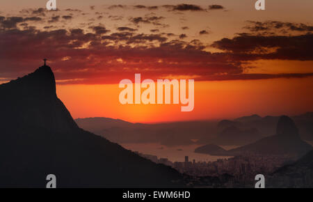 A view of Christ the Redeemer (Cristo Rendentor) atop Mount Corcovado and Sugarloaf (Pao de Acucar) at sunrise in - Stock Photo