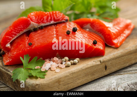 Close up front shot of fresh Copper River red salmon fillets on cutting board, sea salt and herbs. - Stock Photo