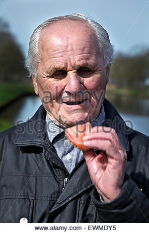 portrait of senior 88 year old man with dentures in his hands - Stock Photo